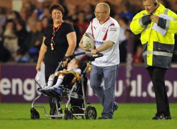 Chris pushes his son Elliott onto the pitch at the St Helen's rugby league the day Elliott got to be the mascot