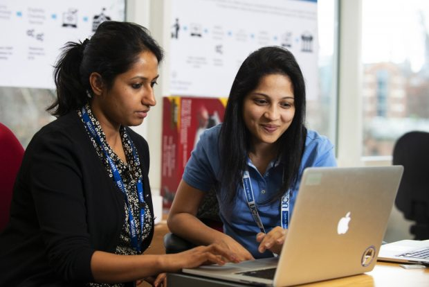 Two female DWP colleagues look at a computer screen