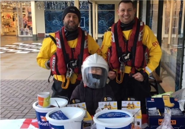 Dareen and Chris stood at a table with a bucket collection for the lifeboat fund