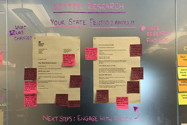 Two example client letters stuck on a glass chanson wall and annoyed with small post-it notes highlighting areas for improvements or changes.