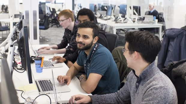 4 male colleauges working at computers together