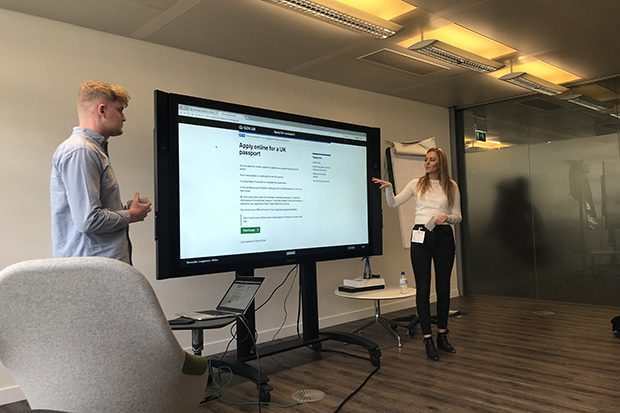 Two students standing at either side of a large display screen. On the screen is displayed the homepage for the Apply online for a UK passport website