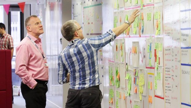 Two male colleagues talking at a whiteboard pointing at a group of Post-It Notes on the wall
