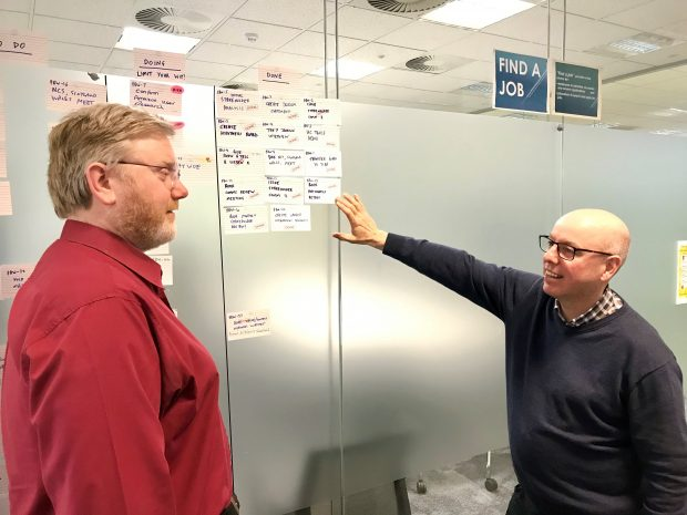 Colleagues Barry and Sean discussing the Find a Job service stood at a working board