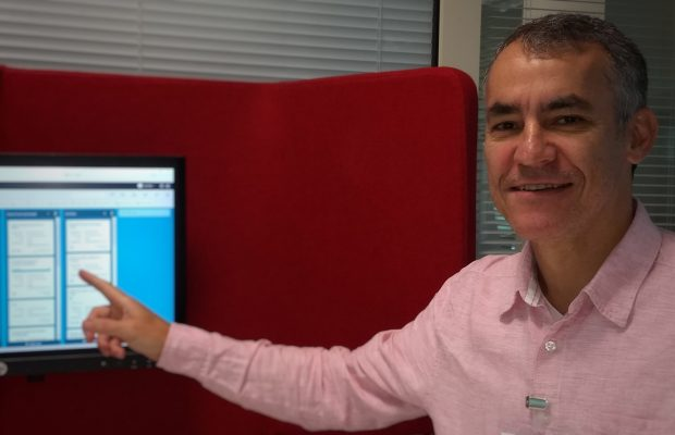Portrait photo of Luiz pointing at a computer monitor