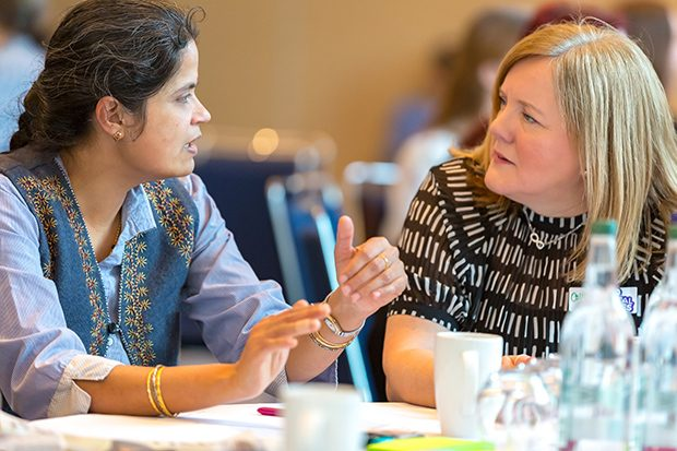 Rasmi and Collett talk at a table at the Digital Voices launch event in Manchester.