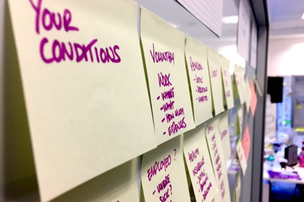 Post-it notes on a whiteboard with writing on including 'your conditions', 'voluntary work', 'employed?', health insurance'