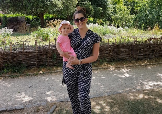 Kirsty stands in garden holding her baby daughter in her arms