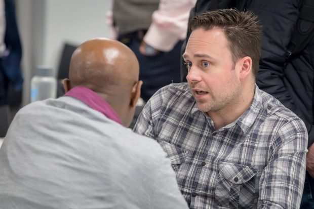 Aaron Jaffery, host of the Women in Digital conference, talks to a male colleague at a table.
