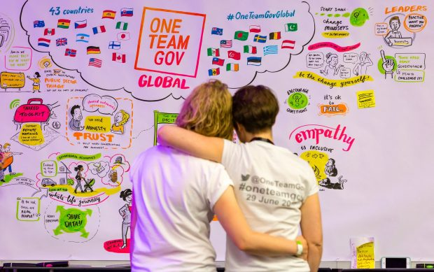 2 people hugging in front of a OneTeamGov colourful display