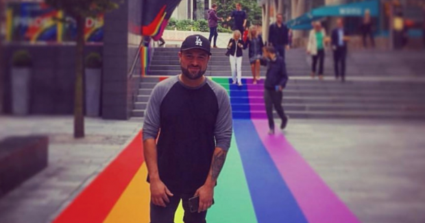 Taran standing on a rainbow coloured carpet