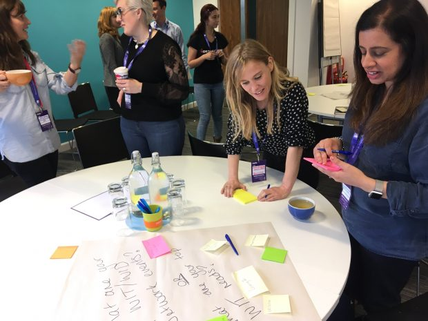 Attendees taking part in a table exercise with pens and post its