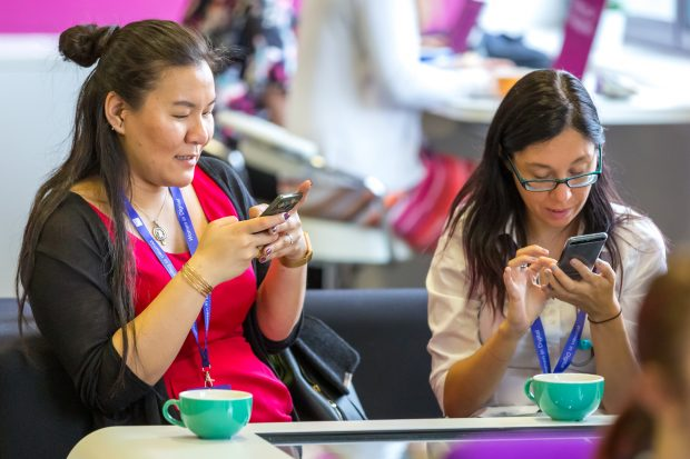 Photo showing Jenny Murray and Zoe Gould on mobile phones interacting with Slido questions during the event