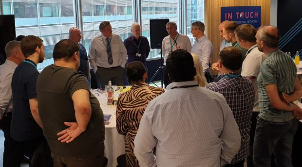 Group of people stood around a table at the SRE meet-up discussing ideas.