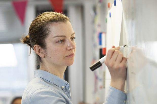User researcher writing on a whiteboard