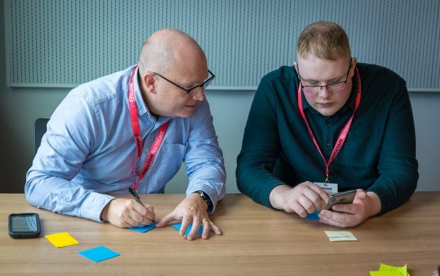 Mark and another DataJam attendee capturing ideas on post-its and mobile phone