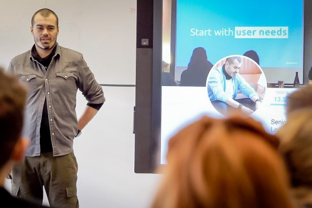 Craig Abbott, DWP Digital's Head of Accessibility stood up giving a talk on accessibility in service design at DWP's Newcastle Hub during Services Week 2019, in front of an audience of people, with a display screen behind him