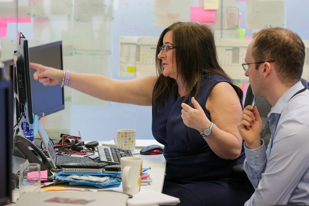 DWP Digital's Head of Integration, Jacqui Legetter at a desk with a colleague looking at a computer screen