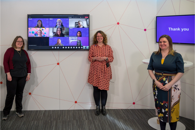Three women stand smiling in front of a television screen that features eight women's faces