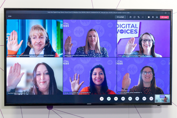 Six women are shown on a computer screen raising their hands