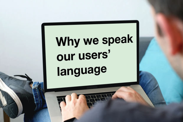 A man sits with a laptop open on his legs. The screen of the laptop shows the blog title 'Why we speak our users' language'