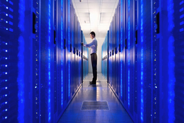 A man is standing in a corridor with large computer servers on each side of him