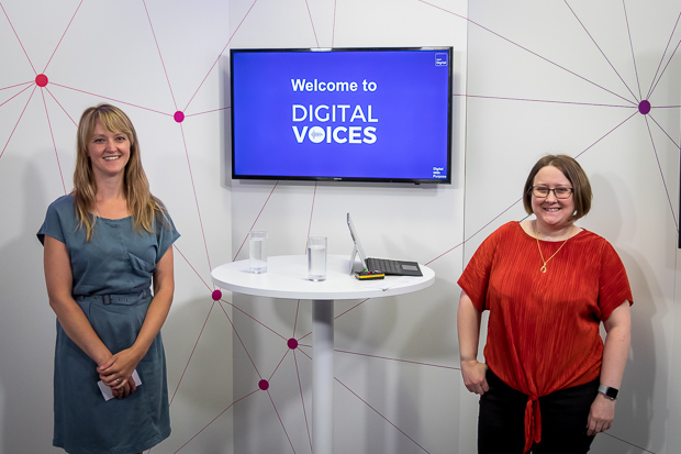 Two women stand smiling in front of a desk and a blue television screen. One is wearing a blue dress, the other has glasses and is wearing a red top and black trousers.