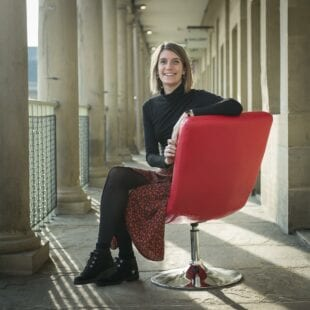 Chloe Williams sitting in a red chair on a balcony